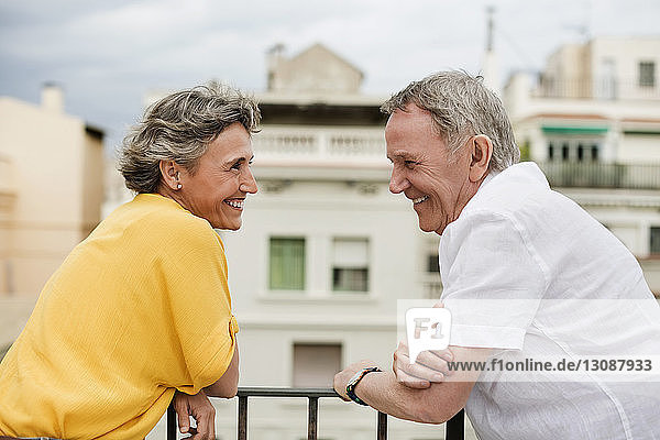 Side view of cheerful senior couple standing on terrace