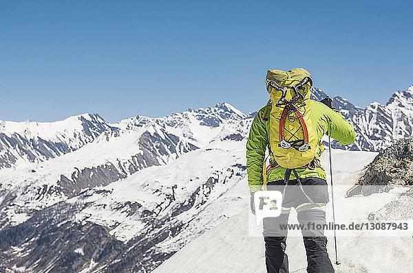 Rückansicht eines Wanderers  der einen schneebedeckten Berg bei strahlend blauem Himmel an einem sonnigen Tag besteigt