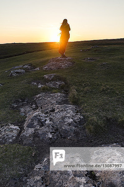 Rear view of woman standing on grassy hill against sky during sunset