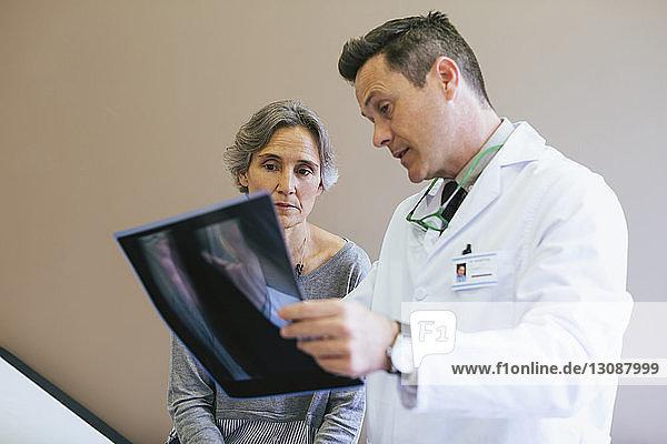 Nahaufnahme eines Arztes  der dem Patienten in einer medizinischen Klinik das Röntgenbild erklärt