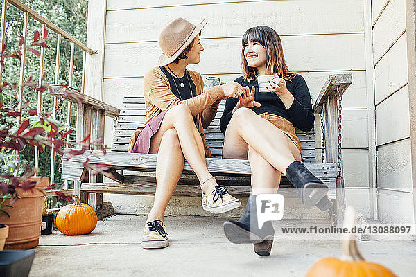 Freundinnen unterhalten sich in voller Länge  während sie auf einer Holzbank in der Veranda sitzen