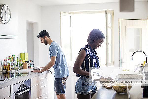 Seitenansicht eines in der Küche arbeitenden Paares