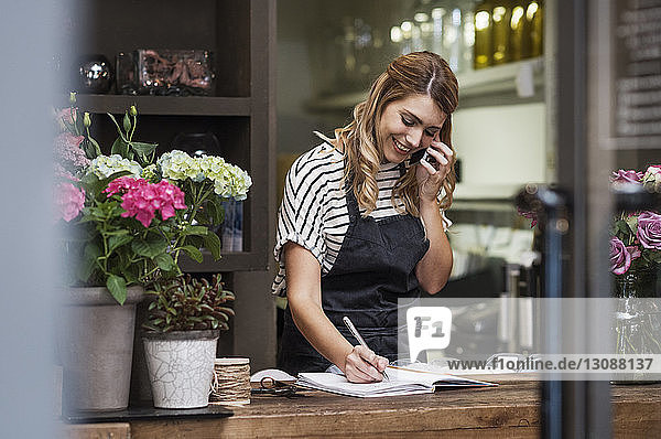 Florist writing in note pad while using mobile phone