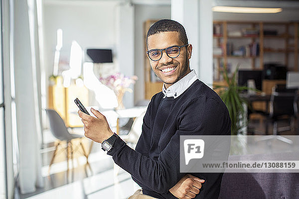 Portrait of smiling businessman using smart phone while leaning on sofa in office