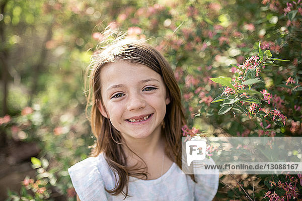 Close-up portrait of happy girl standing by plants at park