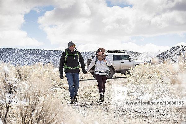 Paar in voller Länge an den Händen haltend beim Spaziergang in der Wüste vor bewölktem Himmel im Winter