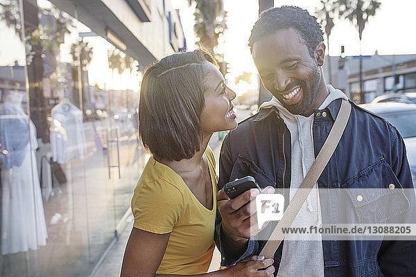 Woman looking at man using phone on sidewalk