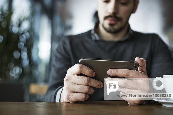 Geschäftsmann benutzt Smartphone  während er im Café sitzt