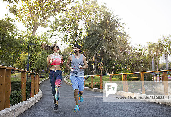 Smiling couple talking and jogging at park