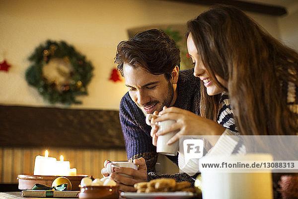 Lächelndes Paar trinkt an Weihnachten Kaffee bei Tisch