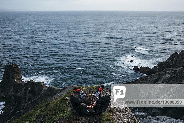 Hochwinkelansicht eines Wanderers  der mit den Händen hinter dem Kopf auf einer Klippe vor einer Meereslandschaft sitzt