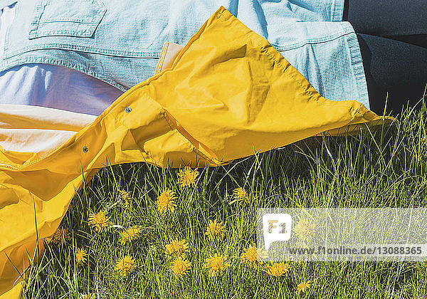 Midsection of carefree young woman lying on grassy field at park