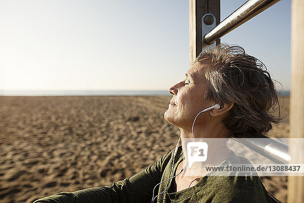 Woman listening to music while resting by gymnastic bars at beach