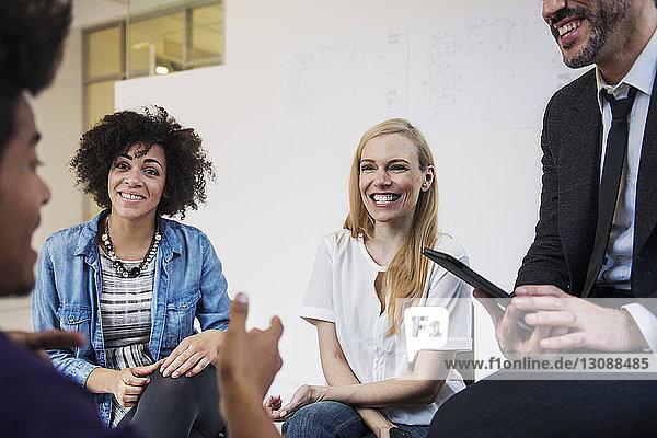 Fröhliche Geschäftsleute schauen Kollegen während der Besprechung im Büro an