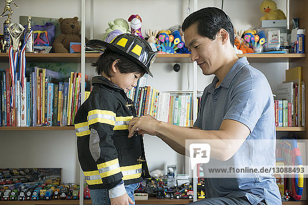 Father helping son in wearing costume at home