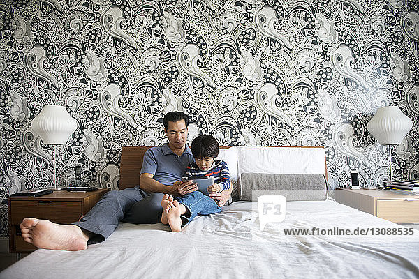 Father and son using tablet while lying on bed at home