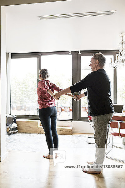 Senior man assisting woman in doing yoga at home
