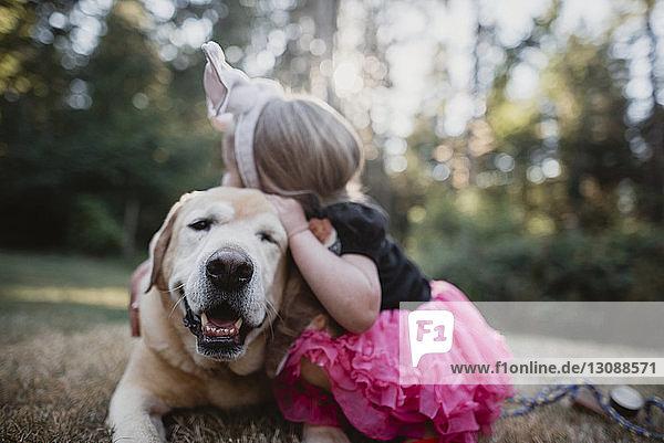 Verspieltes Mädchen umarmt Hund auf dem Feld Verspieltes Mädchen umarmt Hund auf dem Feld