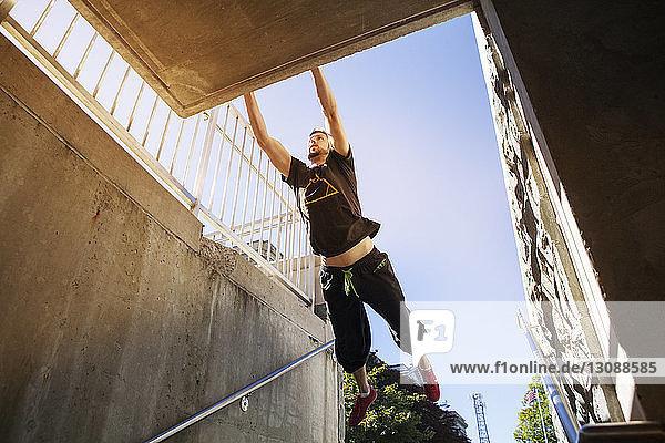 Niedrigwinkelansicht eines auf dem Dach hängenden Mannes bei klarem Himmel