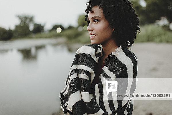 Seitenansicht einer nachdenklichen  in ein Tuch gehüllten Frau  die am Seeufer wegschaut