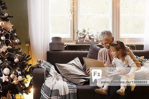 Happy grandmother and granddaughter using laptop while sitting on sofa at home