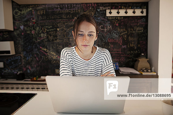 Concentrated woman using laptop at table