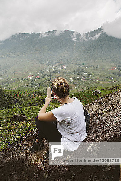High angle view of woman photographing landscape with smart phone