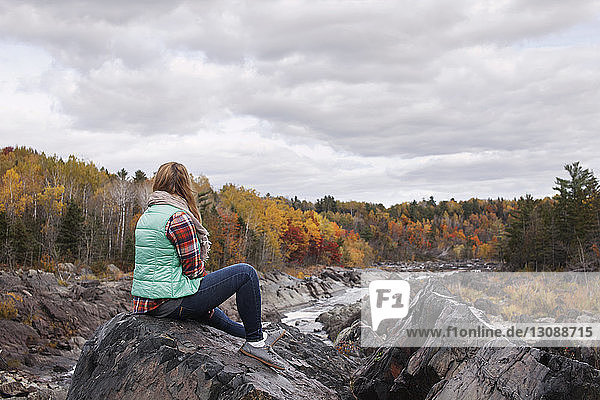 Woman sitting on rock at Jay Cooke State Park against cloudy sky