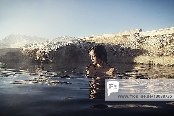 Thoughtful woman relaxing in Mammoth Lake Hot Springs against sky