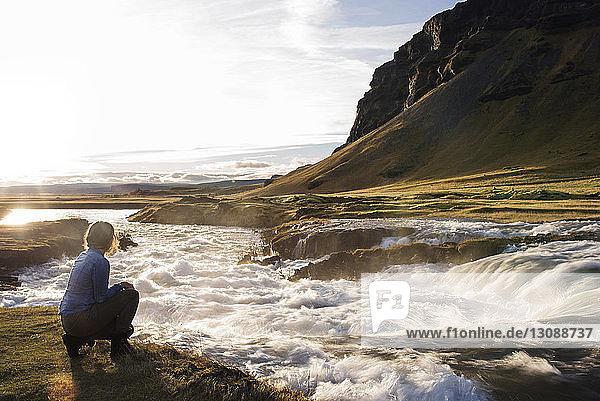 Am Fluss vor Berg und Himmel kniende Frau