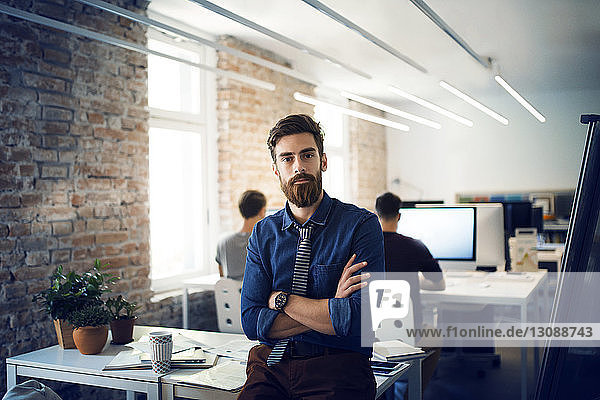 Portrait of businessman with arms crossed leaning on table in office