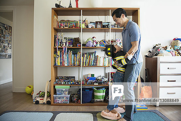 Father playing with boy at home