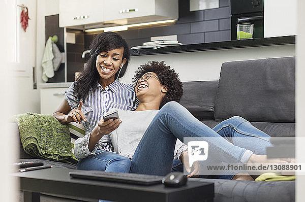 Glückliche Freunde unterhalten sich  während sie zu Hause Musik über ein Smartphone genießen
