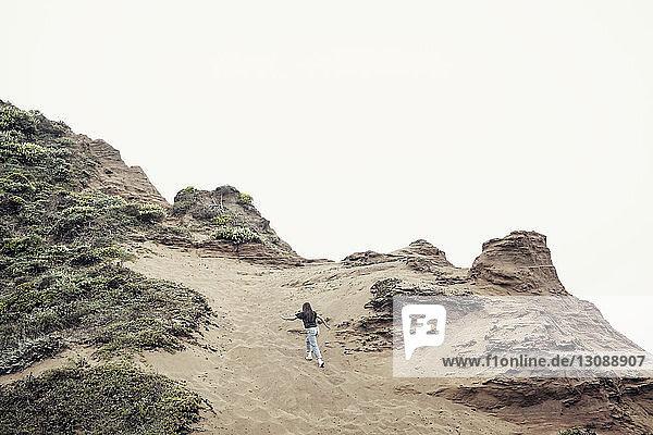 Niedrigwinkelansicht einer Frau beim Bergsteigen gegen klaren Himmel