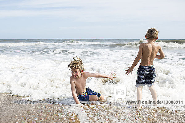 Brothers enjoying at beach against sky during sunny day