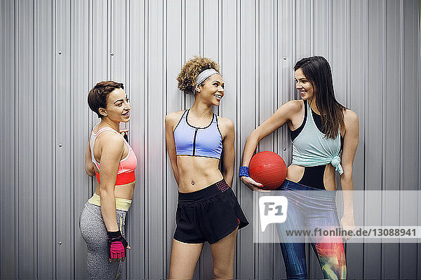 Happy female athletes talking while standing against corrugated wall
