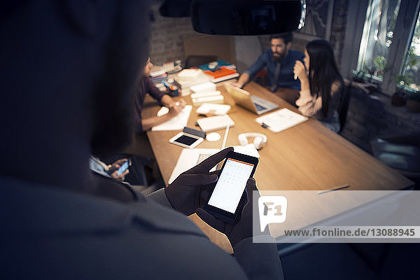 Cropped image of businessman using phone while colleagues discussing in background