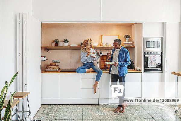 Glückliches multiethnisches Paar in voller Länge beim Essen von Salat und Sandwich in der Küche