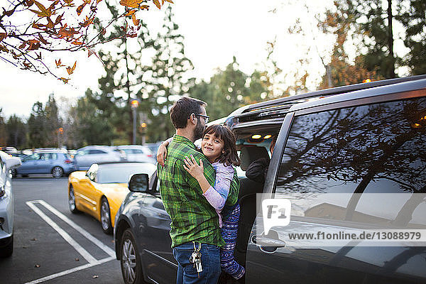 Man carrying daughter while entering car on street