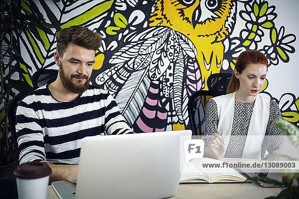 Geschäftsleute mit Laptops am Schreibtisch im Kreativbüro