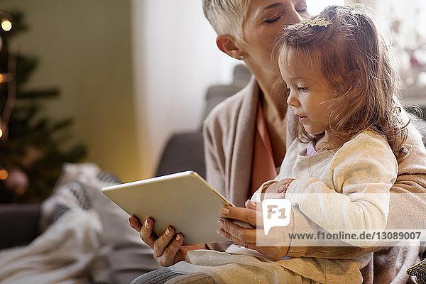 Großmutter küsst Enkelin  während sie zu Hause einen Tablet-Computer hält