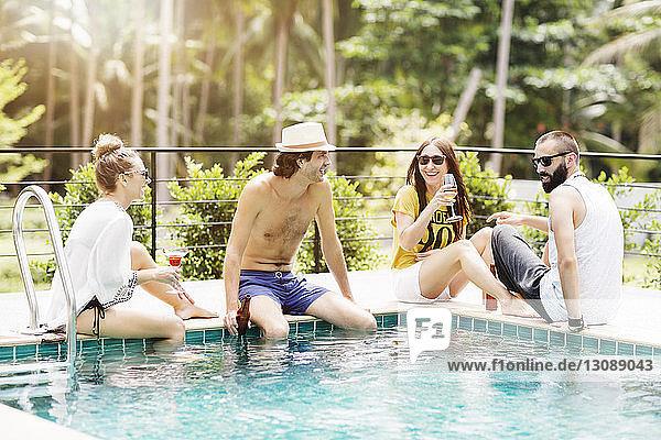 Fröhliche Freunde bei einem Drink am Pool