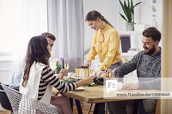 Lächelnde Frau schneidet Kuchen an  während Freunde bei einer Party am Esstisch sitzen