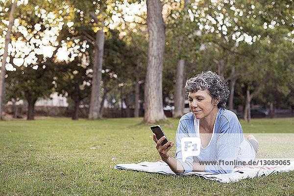 Mature woman using phone while lying on grassy field