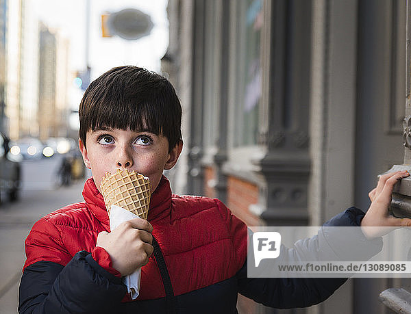 Boy looking up while eating ice cream on footpath in city