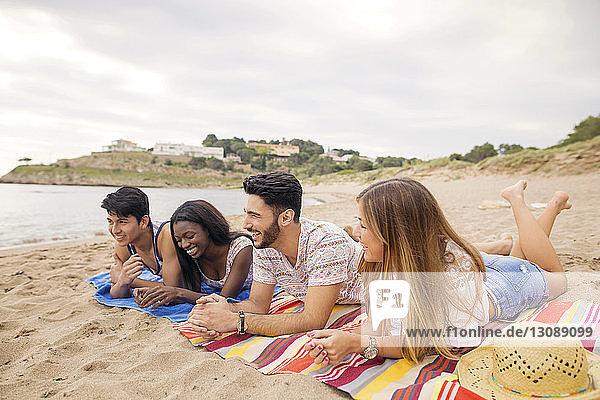 Glückliche multiethnische Freunde entspannen sich an der Küste am Strand