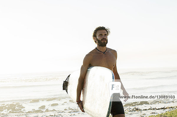Shirtless man carrying surfboard while walking at beach against clear sky