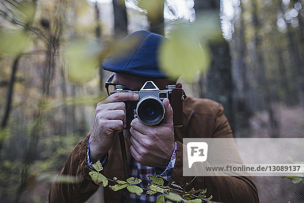 Close-up of man photographing in forest