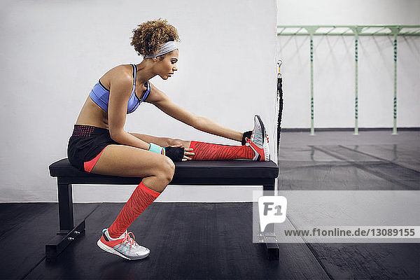 Side view of female athlete exercising while sitting on bench at gym