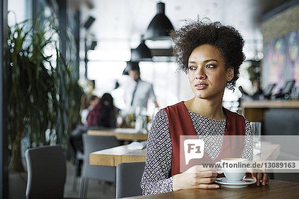 Nachdenkliche Frau hält Kaffeetasse im Café